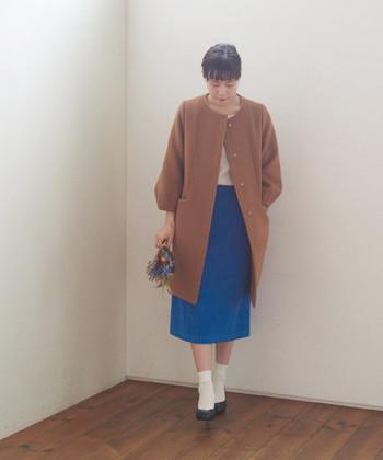 ブラウンのノーカラーコートに、青色のタイトスカートと白色トップスを合わせた着こなしです。青×茶は少し上級者向けに感じるかもしれませんが、全て柄なしのシンプルアイテムを選べば、意外と馴染んでくれますよ。