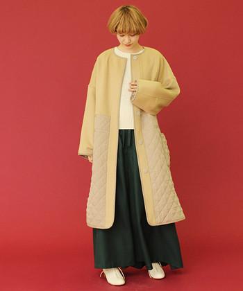 ウールとキルティングの異素材を合わせた、デザイン性の高いノーカラーコートです。膝下まである長め丈のコートなので、暖かさもトレンド感もばっちり。緑のロングスカートとベージュの相性も抜群で、白のトップスとシューズでより柔らかい印象に。