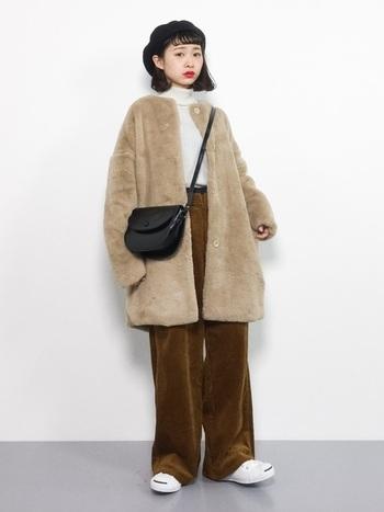 ファー素材のノーカラーコートに、ベロアパンツを合わせた季節感たっぷりの着こなしです。トップスと足元は白色で合わせ、バッグは黒色をプラス。ベーシックなカラ―でまとめた、シンプルだけどおしゃれなコーデです。