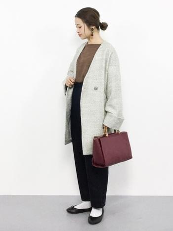 こちらは薄いグレーのノーカラーコートに、茶色のトップスと黒のパンツを合わせた着こなしです。全体的にゆったりとしたアイテムを選び、手元にはボルドーカラ―のバッグをプラスして差し色を上手に使っています。