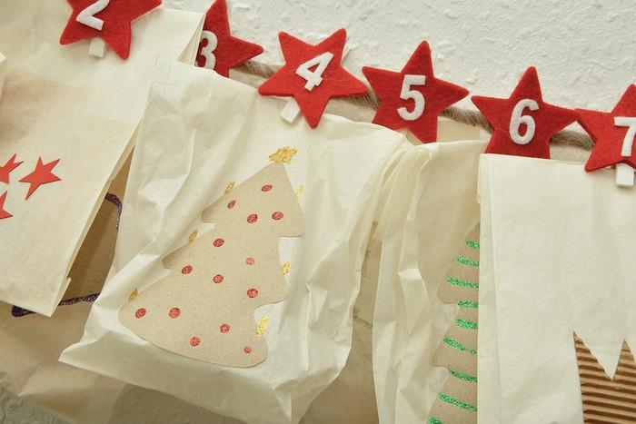 こちらは白い袋にクリスマスらしい絵柄を貼り付け、アドベントカレンダーにしています。フェルトで作った星形のクリップで麻紐にずらりと留めて完成です。