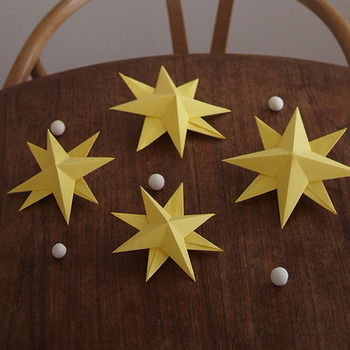 黄色の画用紙を使って星の立体オーナメントを作り、紙粘土で白いボールを作りました。こちらのお星さまは二枚の画用紙を折り紙のように折り、ボンドで貼り合わせています。