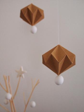 クラフト紙を折って作ったペーパーオーナメント。一番下には紙粘土で作った白いボールが取り付けられています。落ち着きのある色合いがリビングによく似合います。