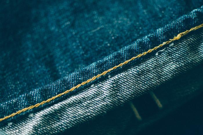 特に裾の処理はジーンズでとても重要なポイントのひとつ。写真は「ユニオンスペシャル」で裾上げしたジーンズ。裏側を見ると鎖のような縫い目ができているのがわかる。これを「チェーンステッチ」といい、洗うことで「パッカリング」という縮みや捻れが生じ、履き込んでいくうちに生地にも独特の表情が生まれる