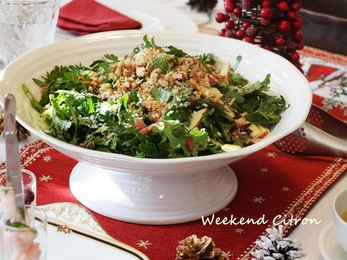 春菊の緑とりんごの赤、クリスマスカラーなサラダのレシピです。冬が旬の春菊は、丁度クリスマスシーズンがおいしい時季。サラダにしてもモリモリ食べることができます。仕上げの粉チーズが、雪のようで綺麗なのも素敵ですね。