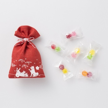 カラフルな飴玉が入ったお菓子袋。表面は、2匹の犬が雪の中で遊ぶ姿が描かれていて微笑ましい。