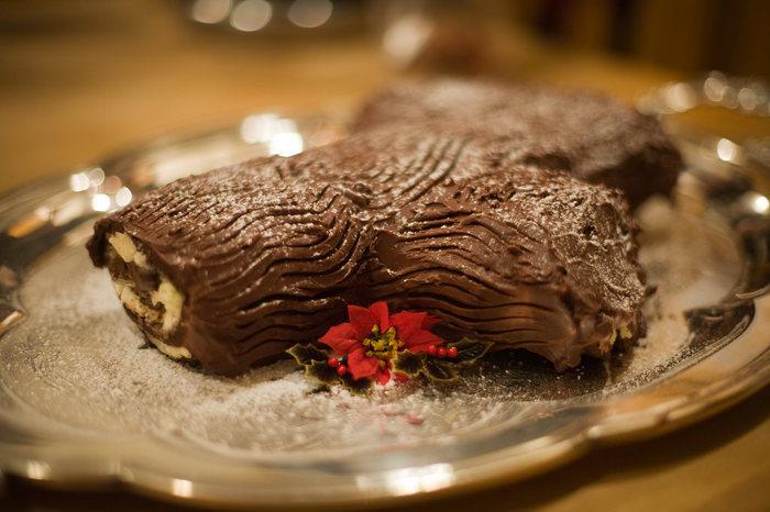"""日本でもお馴染み、切り株の形をしたケーキ bûche de Noël (ビュッシュ・ド・ノエル)は、フランス人がクリスマスイブのディナーの後に食べるデザートとし用意するケーキなんだそうです。! ケーキには""""クリスマスの薪""""という意味があり、その名の通り、薪の形をしています。 どうして薪の形をしているかというと、いくつか説があり、クリスマスの前夜に大きな薪を暖炉で燃やす習慣から来ていると言われています。薪に火をつける際、ブドウの収穫を願いワインをかける地域もあったそうなんです。燃えた後に残った薪は、家を雷から守るために取っておき、灰は畑に蒔くというしきたりがあったんだとか。ところが、時代の流れと共に一般家庭からは暖炉が姿を消し、代わりにこのような風習となりブッシュ・ド・ノエルが誕生したと言われています。"""