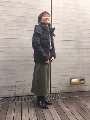 黒のダウンにカーキのラップスカートを合わせたスタイル。シューズと靴下も黒で合わせてかっちりとした印象に。