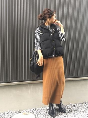 ニットのロングスカートにダウンベストを合わせた着こなしです。ダウンの持つタフな素材感に、ニットスカートの柔らかなニュアンスを加えてフェミニンに。