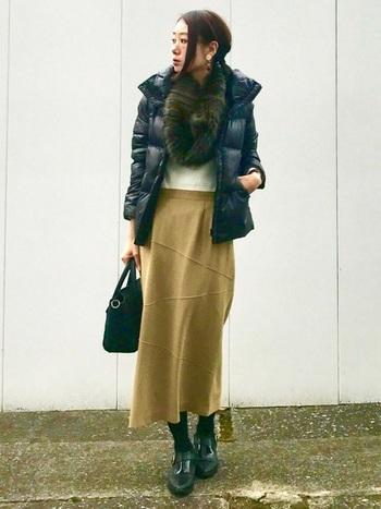 タイトなフレアースカートのフェミニンコーデ。足元はダウンのカラーに合わせて黒で引き締めて、スマートな縦長シルエットに。