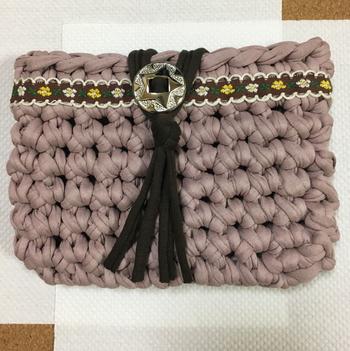 ズパゲッティで作ったポーチは、チロリアンテープとコンチョがアクセント。小花柄のチロリアンテープなのに、大きな編み目のインパクトにも負けないポイントになっています。