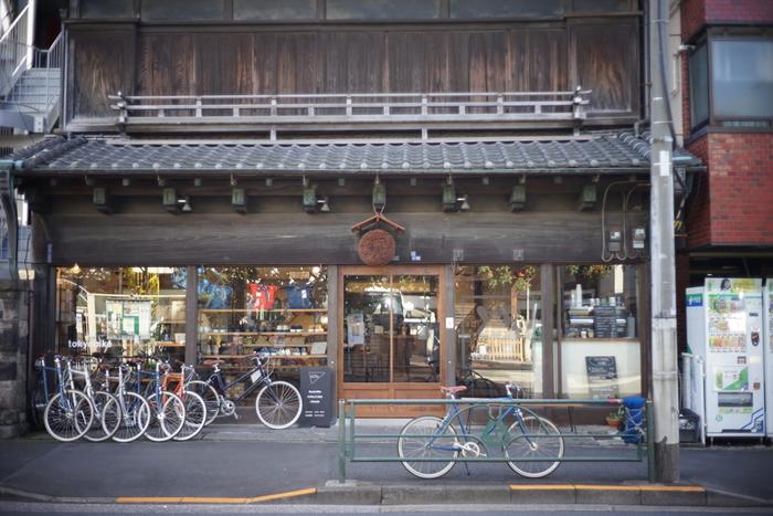 千駄木駅から徒歩7分ほどのところにある「tokyobike Rentals Yanaka」。木造の歴史を感じさせる店構えですが、それもそのはず。築80年以上のかつて酒屋だった建物を改装されたとのこと。レンタルバイクを中心としたお店ですが、それだけではなく、バッグやスニーカーなどグッズ販売や、カフェスペースを併設しています。