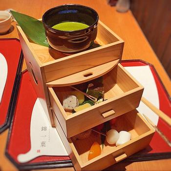 木箱にスイーツが入った『錦一葉フォンデュ』。三段に重なった木箱を開けると、上品に盛り付けられた季節のフルーツやお団子が詰まっています。宇治抹茶ソースにつけて、一つ一つの素材のハーモニーを愉しみましょう。