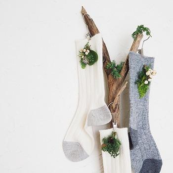 ミニコサージュを「無印良品」の靴下につけて、流木の枝に吊るした「クリスマス靴下」。ナチュラルで落ち着いた色味が大人のイメージ。靴下はもちろん、このあと普通に履くことができますよ。