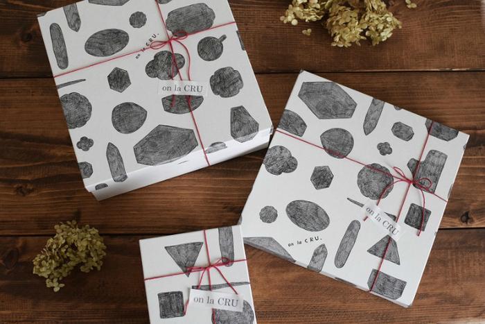 包装紙や紙袋に加えて、サイズが選べる同柄のボックスも。モノトーンに赤のひもが映え、オシャレ感を演出してくれます。
