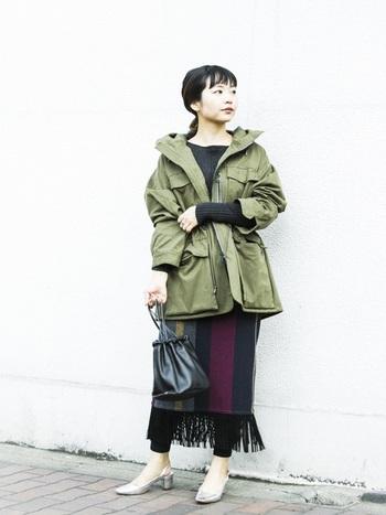 ミリタリー系のダウンジャケットにはフリンジ付きスカートで女性らしさとアクセントをプラスして。シルバーの靴を合わせるとオシャレ感がグッとアップ!