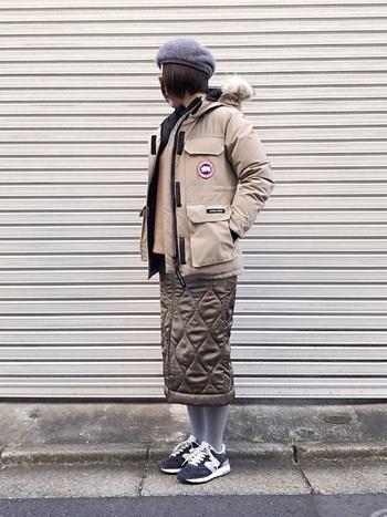 カナダグースのベージュのダウンジャケットにカーキのキルトのスカート、グレーのモヘアベレー帽と同色スニーカーを合わせた暖かコーデ。特に今期は冬でも明るめの優しい配色にそろえるのが◎