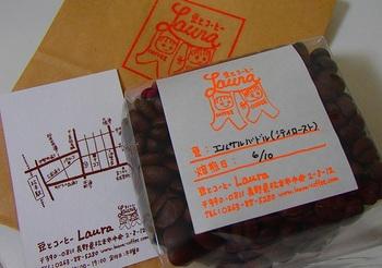 """テイクアウトは100gから。パッケージには、焙煎日と豆の特徴が記載されています。 """"Laura""""の文字にぶら下がるふたりのちびっ子、かわいらしいロゴマークですね。"""