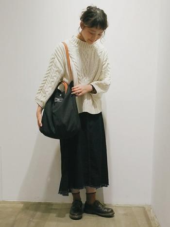 編地が個性的なホワイトニットは、デニムスカートでその魅力を引き立てて。裾の形に捻りが効いたAラインスカートは、使いやすいのに人と差がつく秀逸ボトムです。