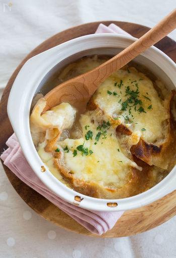 フランスパンとチーズが入ったボリュームたっぷりのオニオングラタンスープ。美味しさの秘訣は、たまねぎを「焦げを水でこそぎ落とすように炒める」事です。チーズが固まらないうちに、熱々を召し上がれ♪