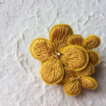 フェルト地に刺繍を施した、ぷっくりと可愛らしい花びら。手作りのぬくもりがいっぱいの花びらを3枚重ねて、立体的なデザインのブローチにしています。シンプルなお洋服に合わせると、そのおしゃれさが引き立ちます。
