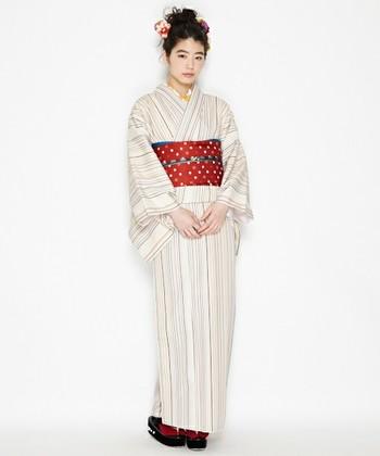 ストライプ柄の着物に赤の帯を合わせて小粋に。初心者さんにはシワになりにくい、こんなポリエステル素材がおすすめ。
