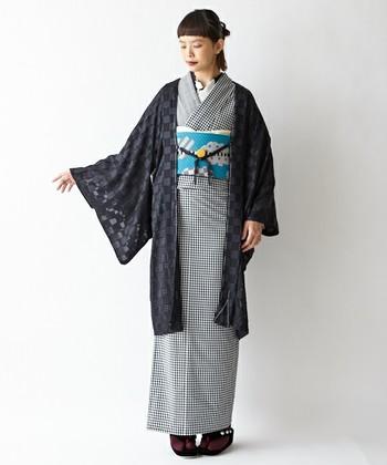 市松模様の着物に同じ柄の薄羽織を合わせ、黄色の帯締めをアクセントにしたアレンジが素敵です。市松模様のような古典柄は年齢関係なく着ることができ、合わせる帯で表情が変わるので、初心者の方は一枚あると重宝する柄かもしれません。