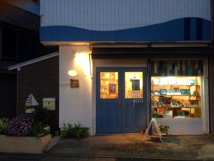 津久井浜駅からほど近い、水色のドアに白い壁が印象的な絵本カフェ「うみべのえほんや ツバメ号」。名前だけでもキュンとくるこのお店は、横須賀で唯一の絵本専門店です。