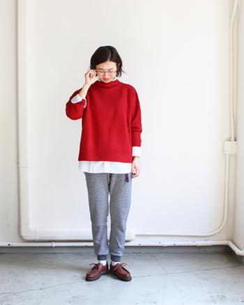 グレーのスウェットパンツに、赤のニットと白シャツをレイヤードしたスタイル。グレー×赤は冬のナチュラルコーデで抜群の相性を持つカラーなので、アイテムを選ばずに合わせやすい組み合わせです。