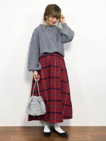 グレーのニットに、チェック柄の赤いスカートを合わせた着こなしです。全体のシルエットをゆるくまとめて、バッグをニットの色と揃えることで繋がりを持たせています。