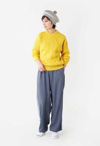 グレーのパンツにイエローのニットを合わせ、明るめカラーのベレー帽・白のシューズをプラス。黄色の鮮やかさが目立ちすぎないよう、上下のアイテムを明るめの色で合わせることで、全体に繋がりを持たせています。