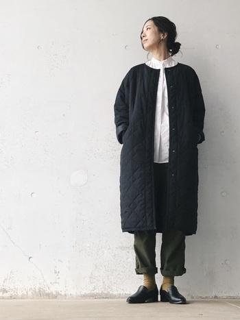 ブラックのキルトコートはホワイトシャツと合わせることでさらにすっきりとした印象に。ノーカラーのデザインも縦長ラインを強調します。
