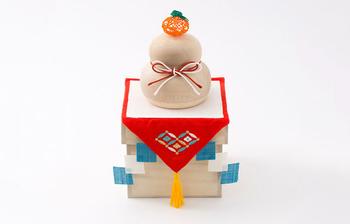 お正月飾りの中でも特にかわいらしい「鏡餅」。 こちらは毎年飾れる木製の鏡餅で、見た目もとってもおしゃれ。水引で作られた「代々栄えるように」と乗せられる橙(だいだい)や、敷き布に「災いを払う」とされる四方紅がアレンジされたりと、きちんと意味も込められています。