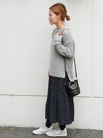 ゆったりニットとロングスカートを組み合わせたゆる感が魅力的なコーデ。フレアのフェミニンなドット柄スカートなら、グレーニットの上品さが引き立ちます。