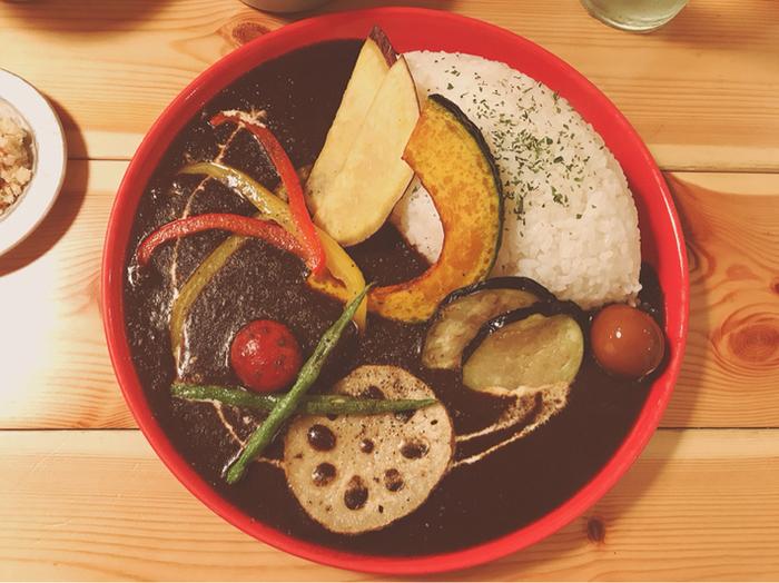 """長崎県の波佐見焼「HASAMI」のつややかな赤いプレートに盛り付けられた「野菜カレー」。カレーに入ったうずらのピクルス、前菜の""""卯の花""""や""""切り干し大根の煮物""""など…。器や副菜も、おうちでの盛り付けの参考になりますね。"""