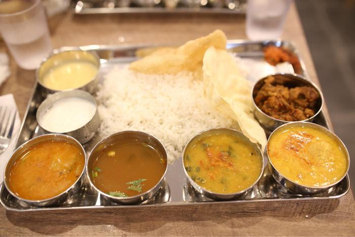 南インドの定食「ミールス」。色とりどりのカレーをライスに混ぜながらいただきます。おうちで何種類ものカレーを用意するのは難しいけれど、揚げ物やサラダ、カレールーなどを小分けにする盛り付けなら真似できそう!