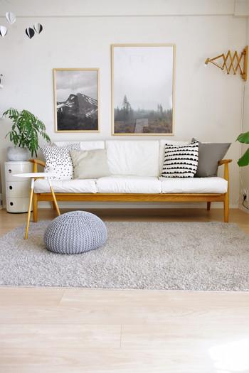 白いソファにグレーやベージュなどの淡い色合いのクッションで優しい雰囲気のインテリア。