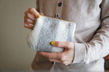 太めのストライプがシンプルながまぐちのフェルトポーチ。羊毛のほんわかとした質感がやさしい印象を与えます。