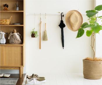 乱雑になりがちな玄関は、常に綺麗に掃除しておきたいもの。そんな時は突っ張り棒を活用して、ほうきや靴べらなどを植物と一緒に吊るしてしまいましょう。白い壁に絵になってお掃除もでき一石二鳥。
