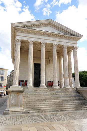 """ニームの街を歩いていると突然遭遇するのが、古代神殿の「メゾン・カレ」。心の準備なく目の当たりにすると、「タイムスリップしてしまったのか!」と驚かされるはず。ちなみに""""カレ""""とはフランス語で「正方形」の意味。その名の通り、四角いのが特徴です。"""