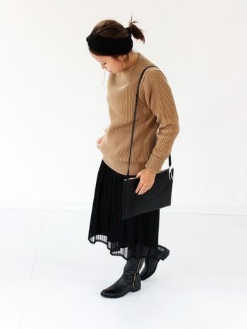 黒を基調としたシックな着こなしが素敵ですね。ブラックベースのコーディネートでも、シアー素材のスカートを取り入れることで柔らかい印象になります。ミディ丈のスカートとロングブーツのバランスが絶妙。