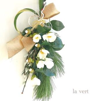 すがすがしい美しさを感じる白い椿。椿は冬になっても葉が落ちずに茂っていることから「繁栄」の象徴として、縁起の良い花とされています。白い花は「浄化」に通じるため、お正月に飾られることが多いんです。  色を抑えたシンプルなスワッグは、新しい年にふさわしいアイテム。見るたびに背筋がぴんと伸びるような気持ちになりますね。
