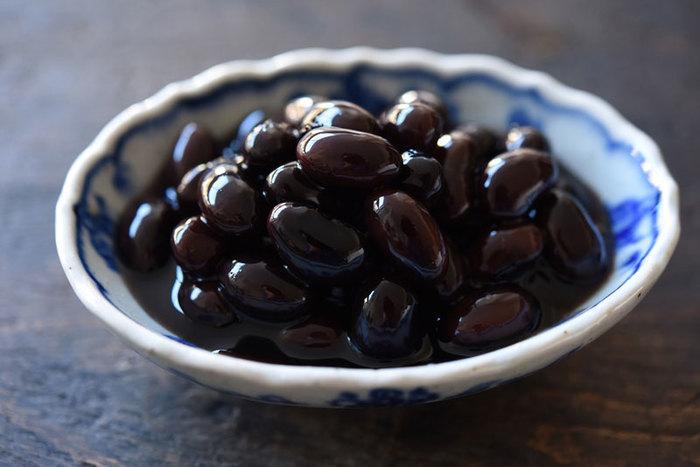 【重曹を用いず簡単に煮上げた『黒豆煮』。黒豆を炊いておけば、弁当やスウィーツに使え便利。正月以外でも作り置きしておきたい常備菜です。】