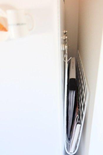 冷蔵庫のちょっとした隙間も、マグネット式のフックでメモ帳などをコンパクトに隠しちゃいます。今すぐ真似したいとっても便利な吊るし収納アイデアですね。
