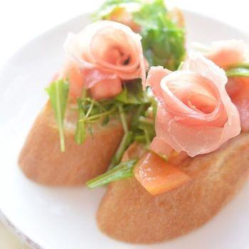 バゲットの上に薔薇の花が。テーブルに並べるだけで華やぐこと違いありません。生ハムをくるくる巻くだけでできてしまうので、手間はそこまでかかっていないのがポイント。