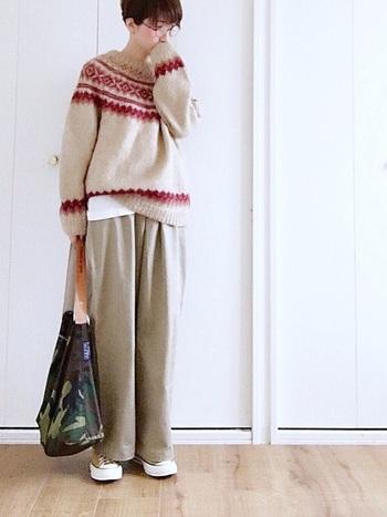 優しいベージュトーンのノルディック柄セーターに同色系のワイドパンツを合わせた上品なコーディネート。あえてカジュアルでメンズライクな迷彩柄バッグを合わせて、雰囲気たっぷりに仕上がっていますね。