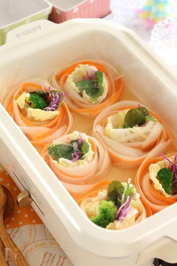 ホームパーティーにもぴったりな華やかで可愛い鍋がこちら。ピーラーでリボン状にスライスしたお野菜を、彩りよく巻いてコンソメスープでコトコト煮込みました。中に巻く具を変えることで、違った味わいにできるのも魅力。いろんなお野菜をクルクル巻いて楽しみたいですね。