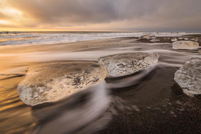 これから訪れる朝のきらめきを予感させるように、黄金色の朝焼けが海や氷に映り込んでいます。