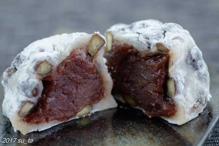 中には少し赤みのある色の餡がぎっしり詰まっています。小豆が程よく形を残したつぶ餡で、北海道十勝産の小豆を使っています。一口食べると、お餅の柔らかさと豆の歯ごたえ、さらに餡の滑らかさが、三位一体となる見事な食感。噛みしめると赤えんどう豆の塩味が餡の甘さと絶妙なバランスで調和し、その味わいに思わずうっとりします。