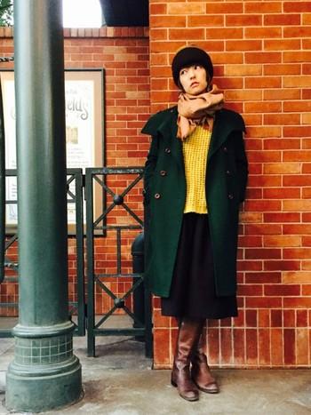 イエローのニットにグリーンのコート。上級者感溢れる色使いのスタイリングは、暗めのブラウンブーツでシックにまとめておきましょう。